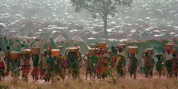 Rwandan refugees carrying water containers